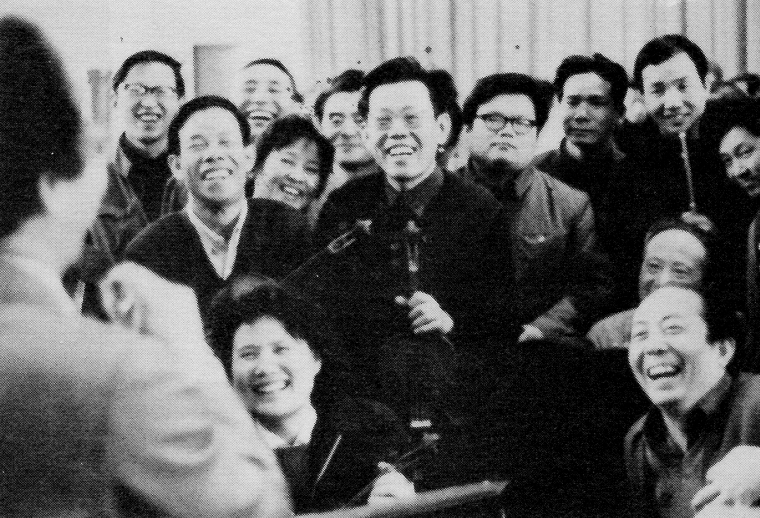 Members of the Central Philharmonic Orchestra in Beijing listen with amusement as Chou Wen-chung greets them