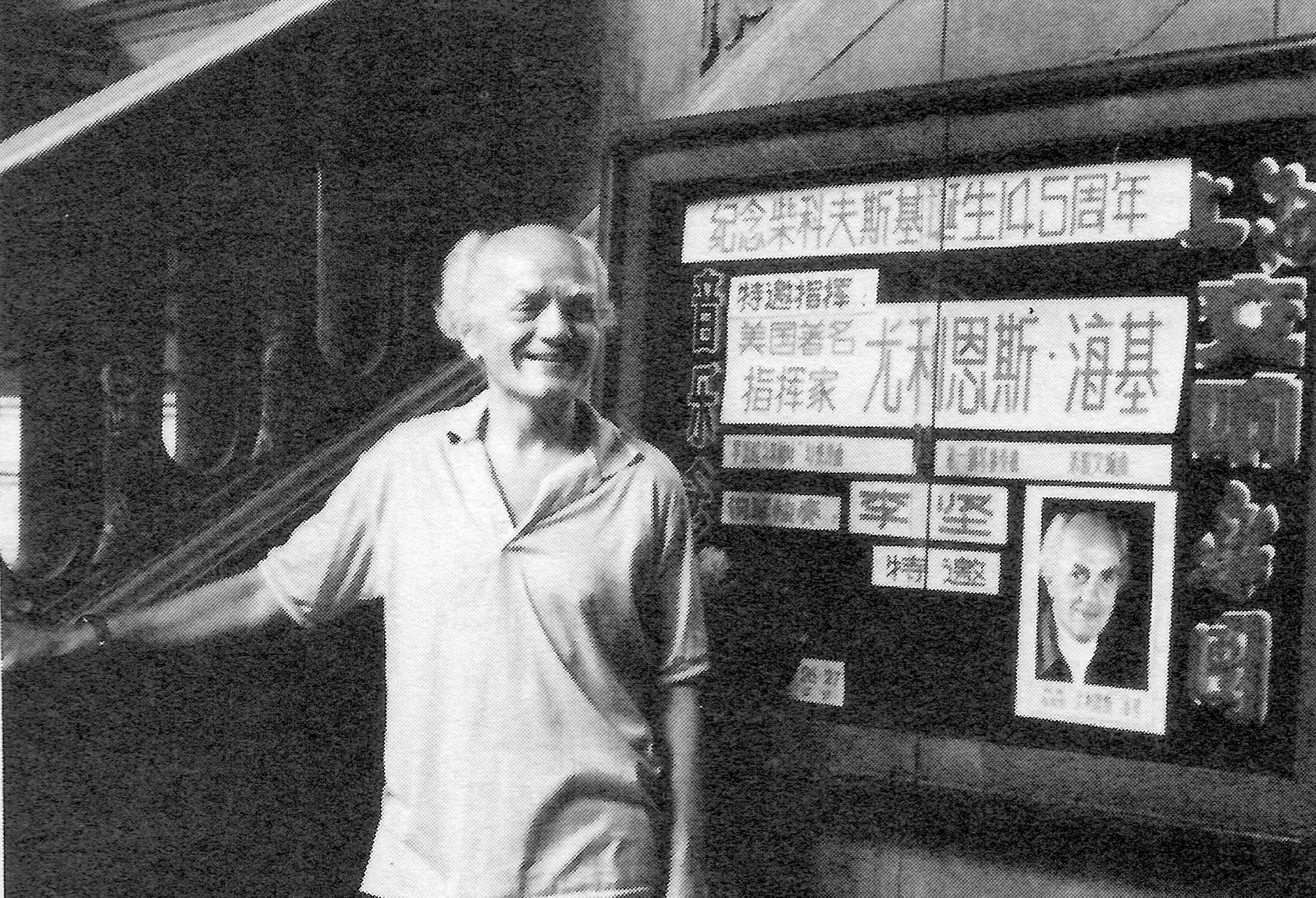 Julius Hegyi in front of Shanghai Symphony publicity announcing an all-Tchaikovsky program featuring pianist Li Jian, and conducted hy Hegyi