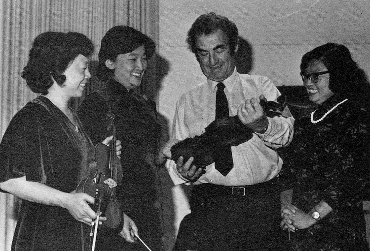 Professor of violin Leonard Felberg examines a Chinese-made instrument with (left to right) Huang Xiaozhi, Yu Lina, and Ding Zhinuo following the Chinese teachers' performance at the University of New Mexico